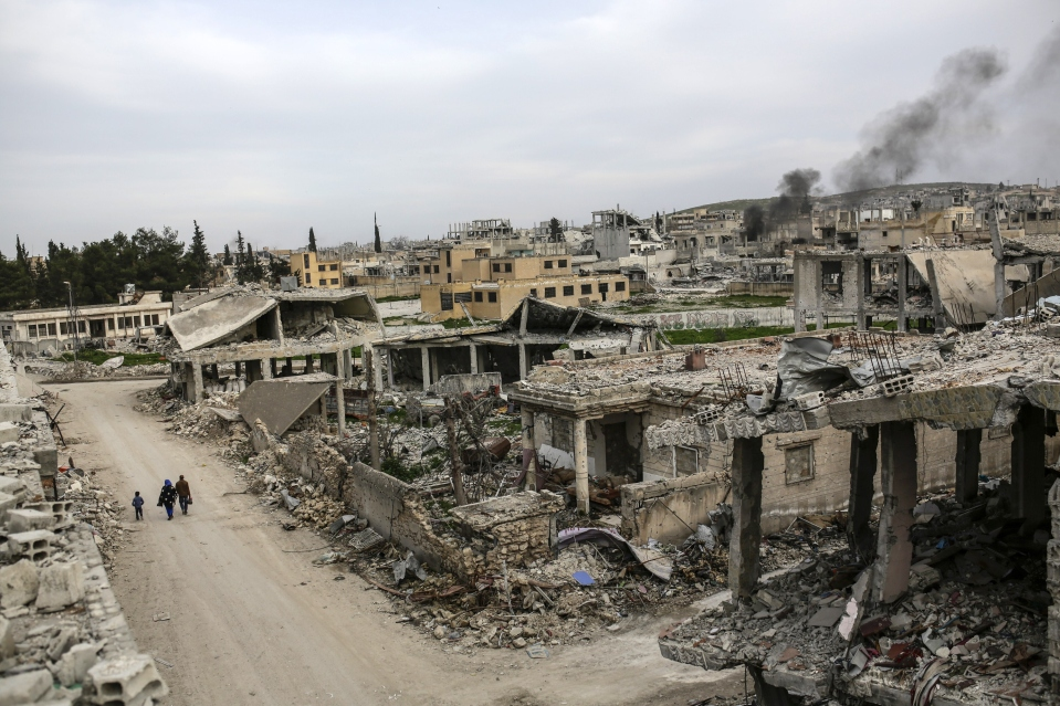 People walk along a conflict damaged street in the Syrian town of Kobane, also known as Ain al-Arab, on March 27, 2015. Islamic State (IS) fighters were driven out of Kobane on January 26 by Kurdish and allied forces. AFP PHOTO/YASIN AKGUL (Photo credit should read YASIN AKGUL/AFP/Getty Images)